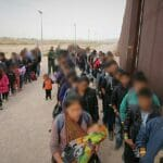 Nota sobre la nueva propuesta del gobierno para mejorar el sistema de asilo en Estados Unidos. La foto es de una fila de inmigrantes junto al muro fronterizo con México.